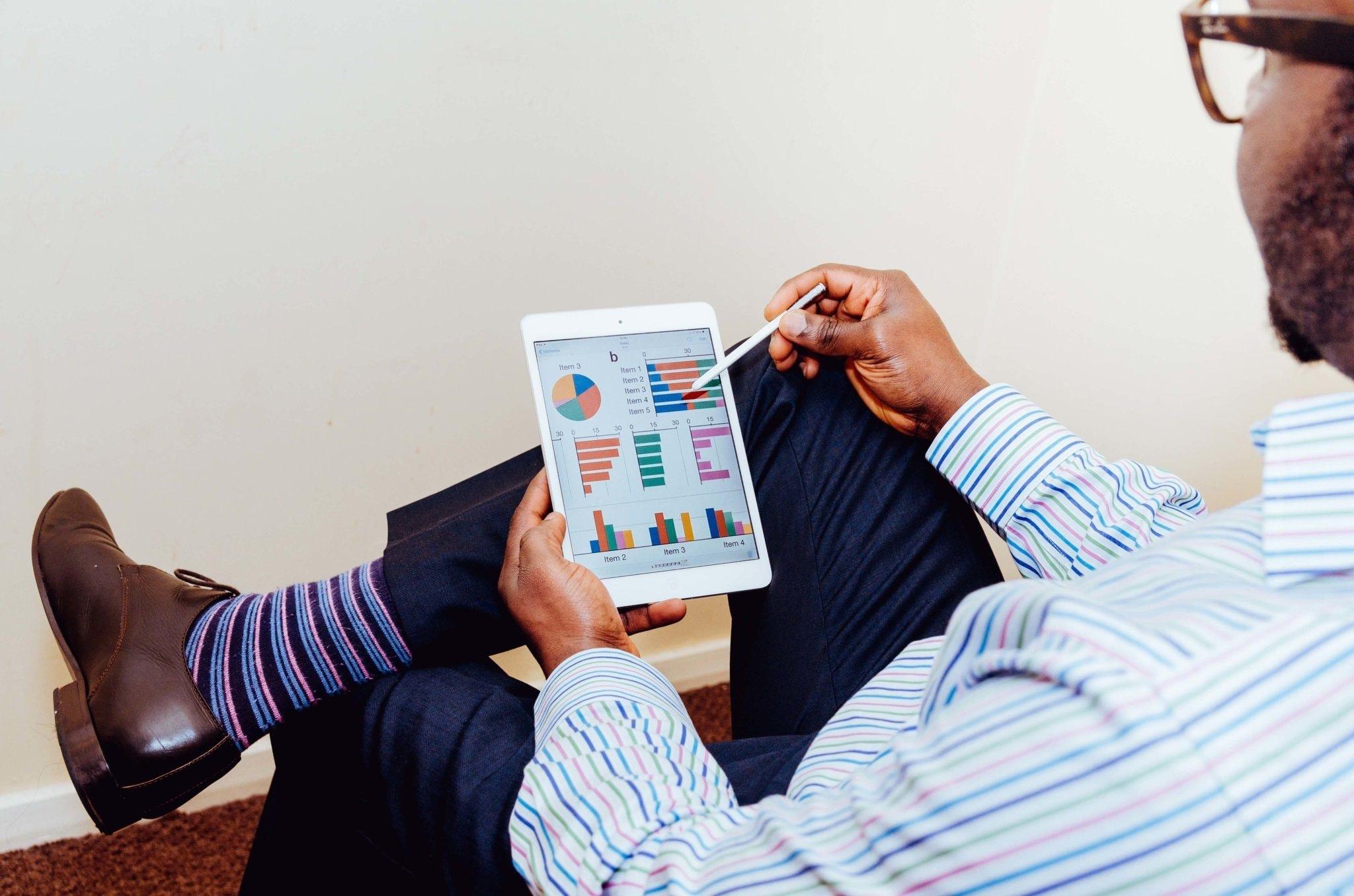 Hombre sentado viendo su tablet con gráficas