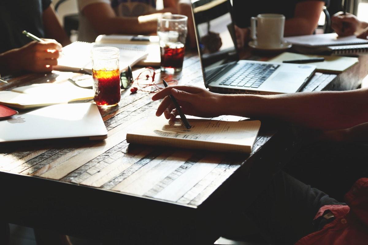 Grupo de personas en una cafetería estudiando