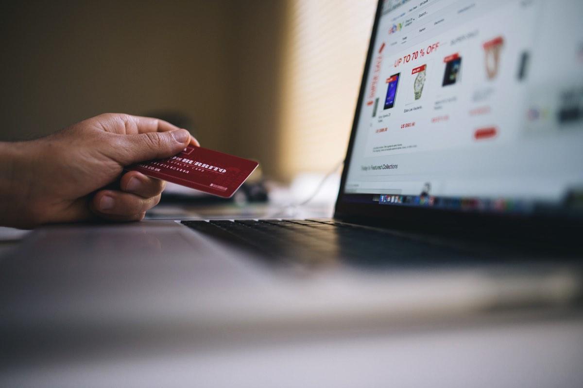 Persona haciendo una compra en línea con tarjeta en mano