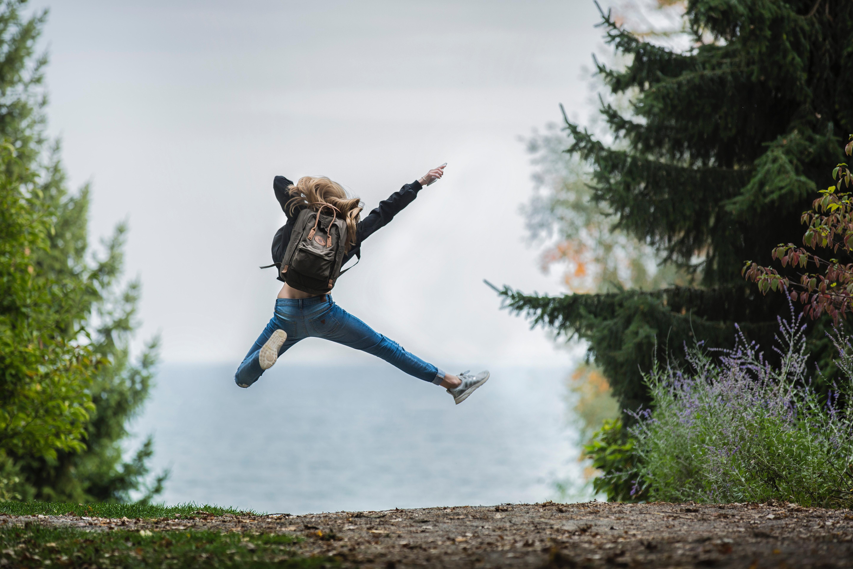 Mujer saltando en el bosque
