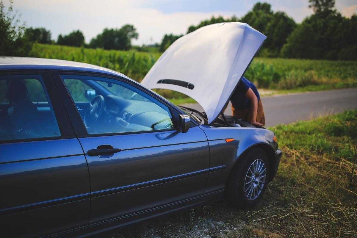 Hombre viendo su carro averiado.